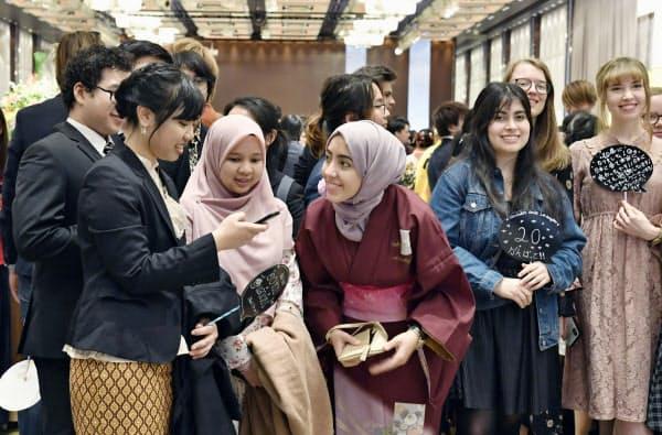 華やかな民族衣装や振り袖姿で成人式に出席し、談笑する外国籍の新成人ら(13日、東京都新宿区)=共同