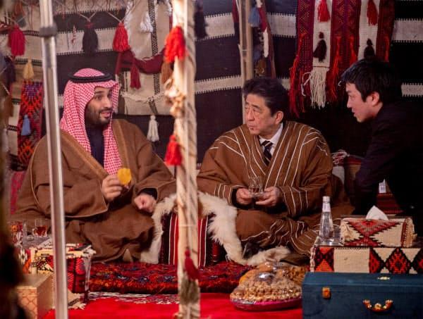 12日、サウジアラビアのムハンマド皇太子(左)の歓迎を受ける安倍首相=ロイター