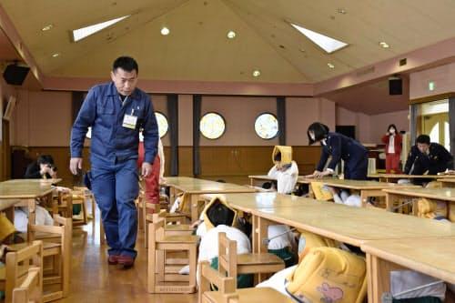 訓練で一斉に机の下に避難した幼稚園児ら(14日、大阪府大東市)=共同