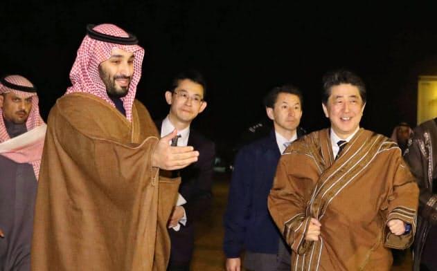 サウジアラビア・ウラー近郊で会談会場に向かうムハンマド皇太子(左)と安倍首相(12日)=代表撮影・共同