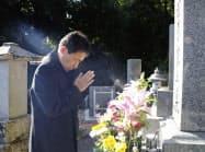 長野県軽井沢町のスキーバス転落事故で亡くなった次男寛さんの墓に手を合わせる田原義則さん(11日、京都府舞鶴市)=共同