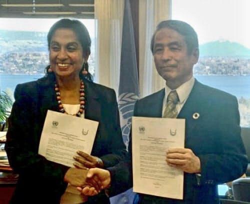 国連貿易開発会議と包括連携協定を結び、握手を交わす岡山大の槙野博史学長(右)=共同