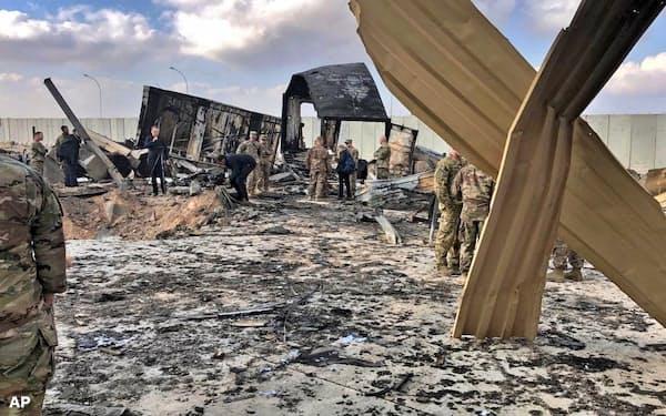 13日、イランからの爆撃を受けたイラクの米空軍基地を調査する兵士ら=AP