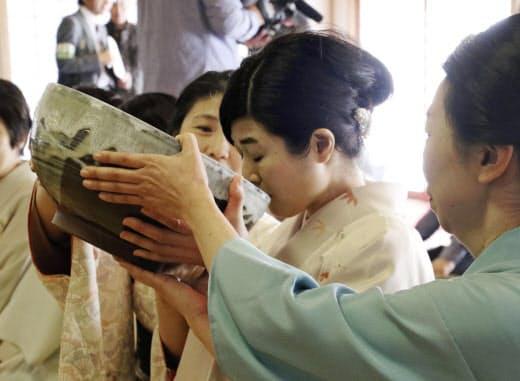 大きな茶わんを支えてもらいながら抹茶を味わう参拝者(15日午前、奈良市の西大寺)=共同