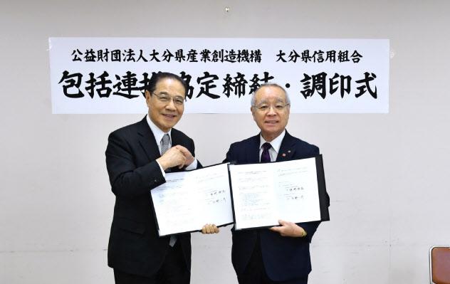 包括連携協定を結んだ大分県信用組合の吉野一彦理事長(左)と大分県産業創造機構の姫野清高理事長(15日、大分市)