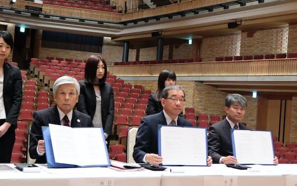 音楽ホールのステージ上で協定書に署名した高垣市長(中)ら(広島県東広島市)