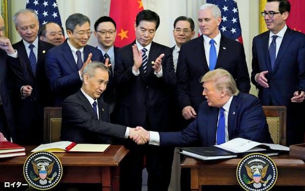 合意文書に署名し握手するトランプ米大統領(右)と中国の劉鶴副首相(15日、ワシントン)=ロイター
