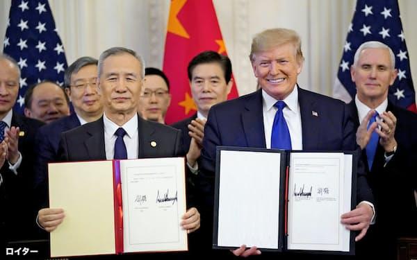 劉氏(左)と第1段階合意に署名し笑顔をみせるトランプ氏(15日、ホワイトハウス)=ロイター