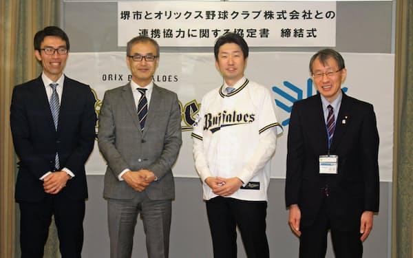 永藤市長はユニホームに袖を通し締結式後の記念撮影にのぞんだ(右から2人目、堺市役所)