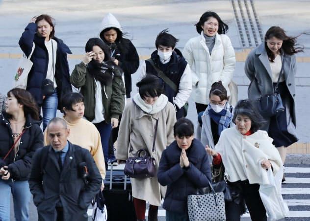 強風の中、町を歩く人たち(2019年12月、名古屋市中村区)