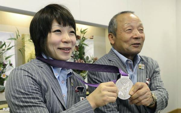 ロンドン五輪から帰国し、銀メダルを手にポーズをとる三宅宏実選手と父の義行コーチ=共同
