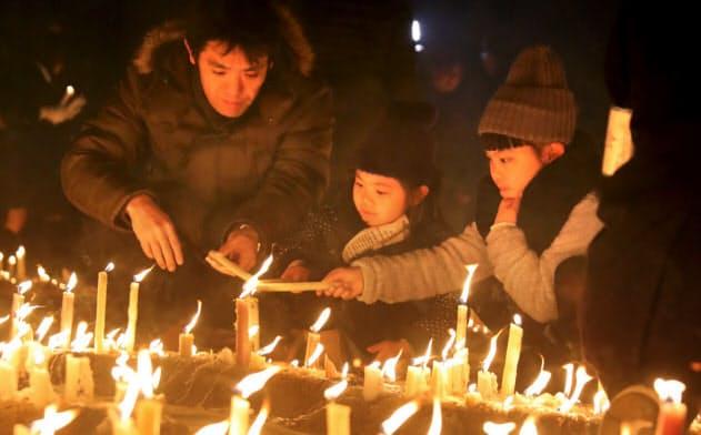 ろうそくに灯をともし、犠牲者の冥福を祈る親子(16日午後、兵庫県伊丹市の昆陽池公園)