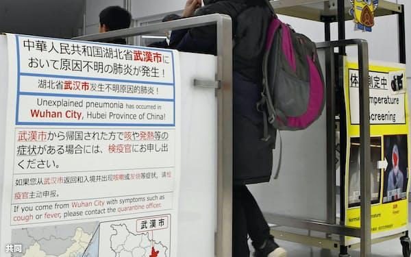 新型のウイルス性肺炎について注意喚起するポスターが掲示された成田空港検疫所を通過する中国湖北省武漢市からの到着客(16日午後)=共同