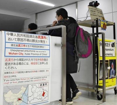新型のウイルス性肺炎について注意喚起するポスターが掲示された成田空港検疫所。中国湖北省武漢市からの到着客が通過していた(16日午後)=共同