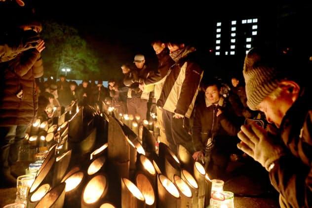 地震発生時刻に黙とうする人たち(17日午前5時46分、神戸市中央区)