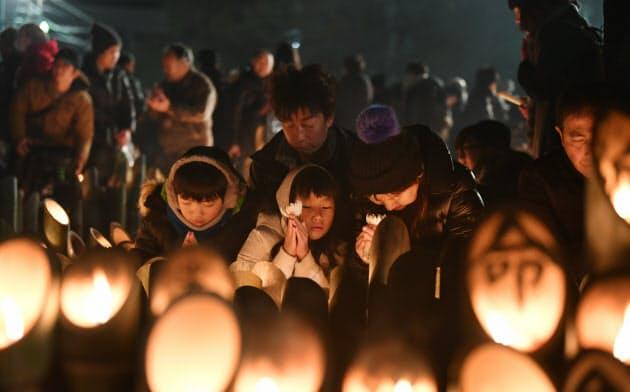 竹灯籠にろうそくの火がともされ、手を合わせる親子(17日午前、神戸市中央区の東遊園地)