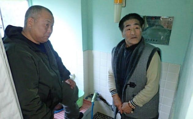 地震で風呂などが壊れながら8年間、損壊した自宅で暮らした横江さん(右)と、支援し続ける伊藤さん(宮城県女川町)