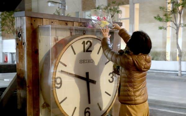 震災から25年、発生時刻を指して止まったままの時計に花を供える人(17日未明、兵庫県西宮市)
