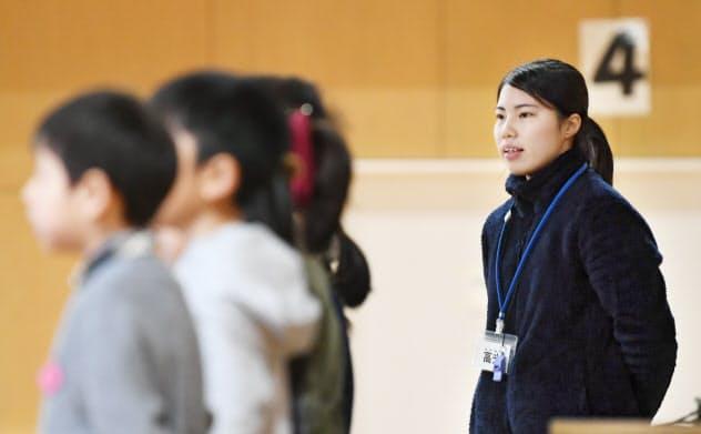 全校防災集会で児童と「しあわせ運べるように」を合唱する小学校教諭の高光愛恵さん(17日、兵庫県芦屋市)