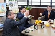 静岡市特産の甘夏を使ったチューハイを試飲する川勝平太知事(中)ら(16日、静岡市)