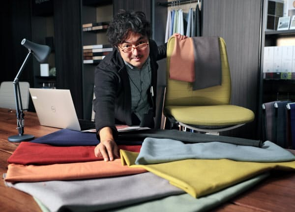生地を並べ、オフィスチェアの色を検討する大木さん=小幡真帆撮影