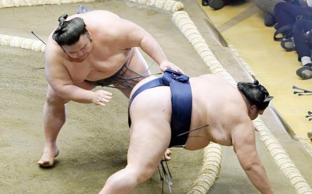 貴景勝(左)が突き落としで御嶽海を破る(17日、両国国技館)=共同