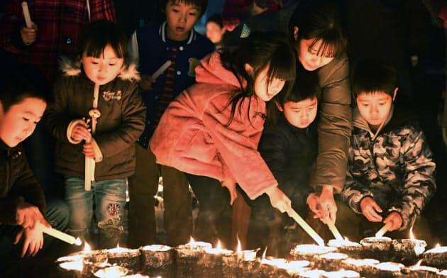 ペットボトルでできた灯籠に火をともす親子ら(17日、神戸市長田区)