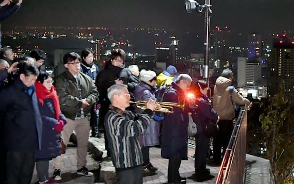 諏訪山公園(神戸市中央区)で開かれた追悼のつどいでトランペットを吹く松平晃さん(手前、17日午前)