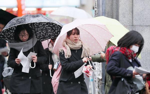 傘を差して、大学入試センター試験の会場に向かう受験生ら(18日午前、東京都文京区の東京大学)