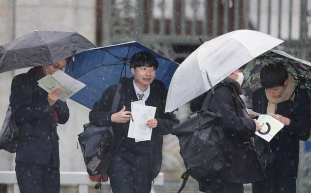 雪が降るなか、大学入試センター試験の会場に向かう受験生ら(18日、東京都文京区の東京大学)