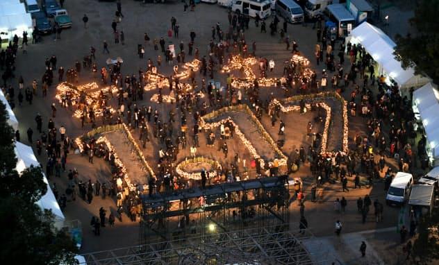 竹灯籠にろうそくの灯がともされ、浮かび上がった「1.17」と「きざむ」の文字(17日、神戸市中央区の東遊園地)