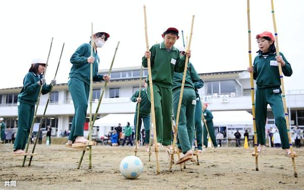 宮城県丸森町立金山小で開かれた竹馬運動会でサッカーをする児童(18日)=共同