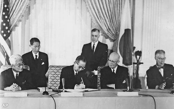 1960年1月、日米安保条約に署名する岸信介首相(中央左)と見守るアイゼンハワー大統領(同右)。左端は藤山愛一郎外相、右端はハーター国務長官=ワシントンのホワイトハウス(AP=共同)