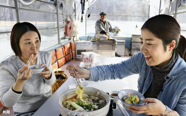台風19号による豪雨被害を受けた「阿武隈ライン舟下り」で、復活した「しし鍋」を堪能する観光客(19日、宮城県丸森町)=共同