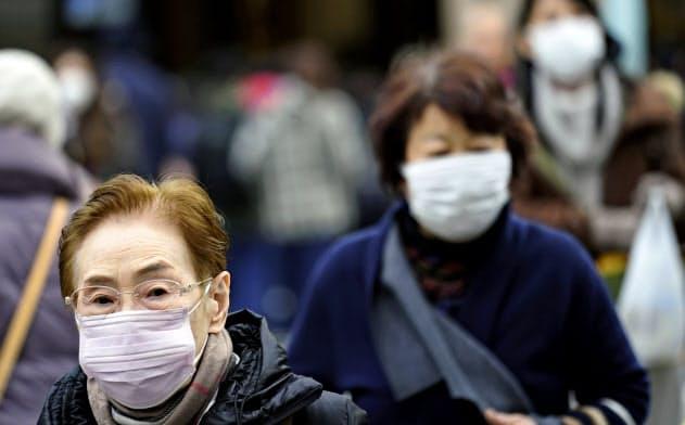 日本でも武漢への渡航歴がある男性のコロナウイルス感染が報告された。マスクをする東京の住民たち=AP