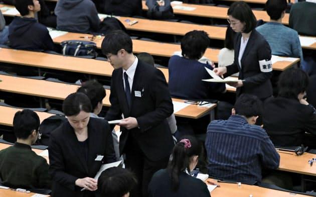 大学入試センター試験の1日目で、受験生に英語のリスニングの問題冊子を配布する担当者=18日午後、東京都文京区の東京大学(代表撮影)