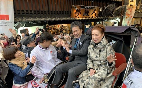 人力車に乗りファンに手をふる役所広司さん(左)と宮本信子さん(19日、松山市)