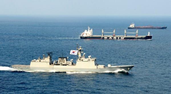 民間船舶を護衛する韓国海軍の駆逐艦(手前)=韓国海軍提供