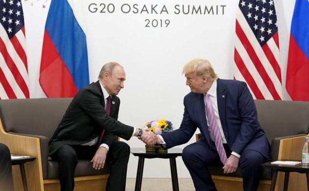 大阪で19年6月に開いた20カ国・地域首脳会議でロシアのプーチン大統領(左)との会談後、握手するトランプ米大統領=ロイター