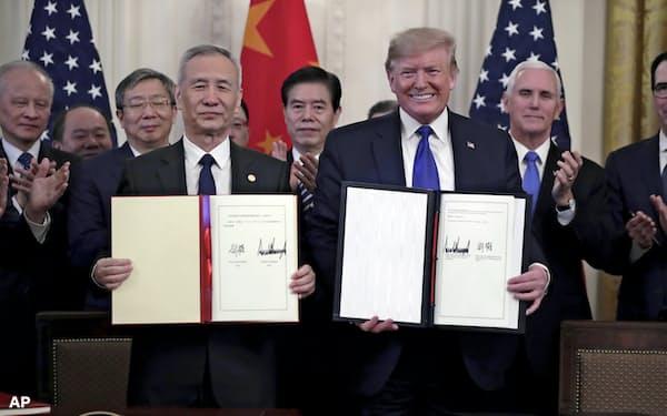 ホワイトハウスで「第1段階合意」にサインしたトランプ米大統領(右)と劉鶴・中国副首相(15日)=AP
