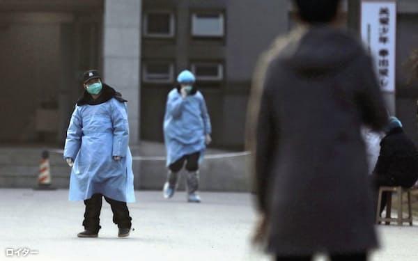 20日、新型肺炎患者が治療を受けている中国・武漢の病院で、マスクを着用した警備員=ロイター
