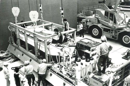 ジンベエザメの輸送テスト中、輸送容器の上に座るのが西田さん(1990年)