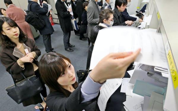 紙の決算資料を配る企業の担当者ら(2月、東証)