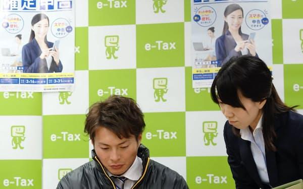 スマートフォンで確定申告を体験する阪神タイガースの北條史也選手(21日、大阪市の大阪国税局)