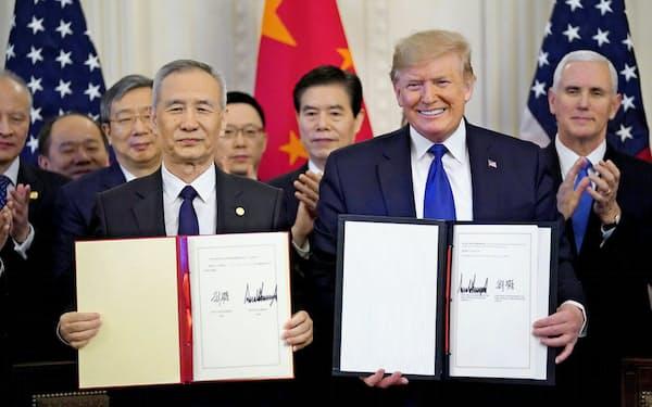 トランプ米大統領と中国の劉鶴副首相(左)が15日、ホワイトハウスで合意文書に署名した=ロイター