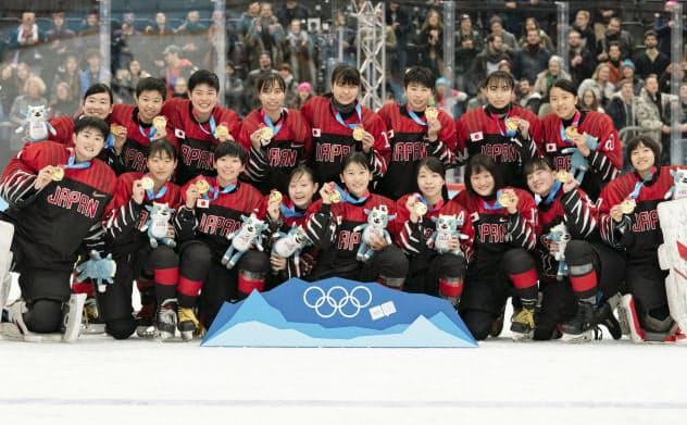 冬季ユース五輪のアイスホッケー女子で優勝し、金メダルを手にポーズをとる日本チーム(21日、ローザンヌ)=OIS提供・共同