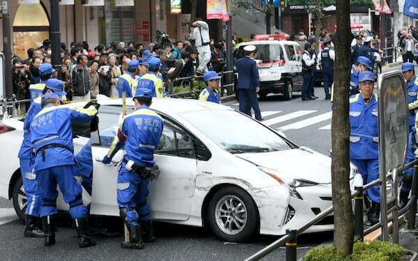 乗用車が歩道に突っ込んだ事故現場を調べる警視庁の捜査員ら(20日、東京都武蔵野市)