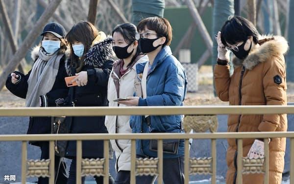 マスクを着用して北京市内を歩く人たち。中国では新型コロナウイルスの感染の拡大が続いている(22日)=共同