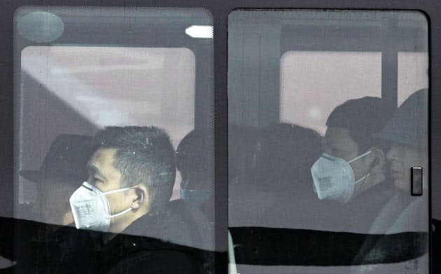 バスの中でマスクを着用する市民ら。中国では新型コロナウイルスの感染の拡大が続いている(22日、北京)=共同