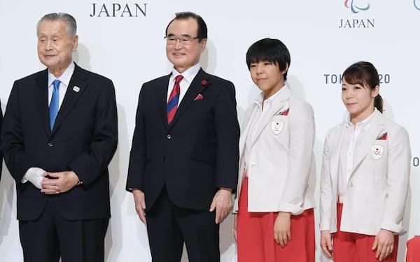 東京五輪・パラリンピック日本代表選手団公式服装の発表会で、選手らと記念写真に納まるAOKIホールディングスの青木拡憲会長(左から2人目)=23日、東京都千代田区